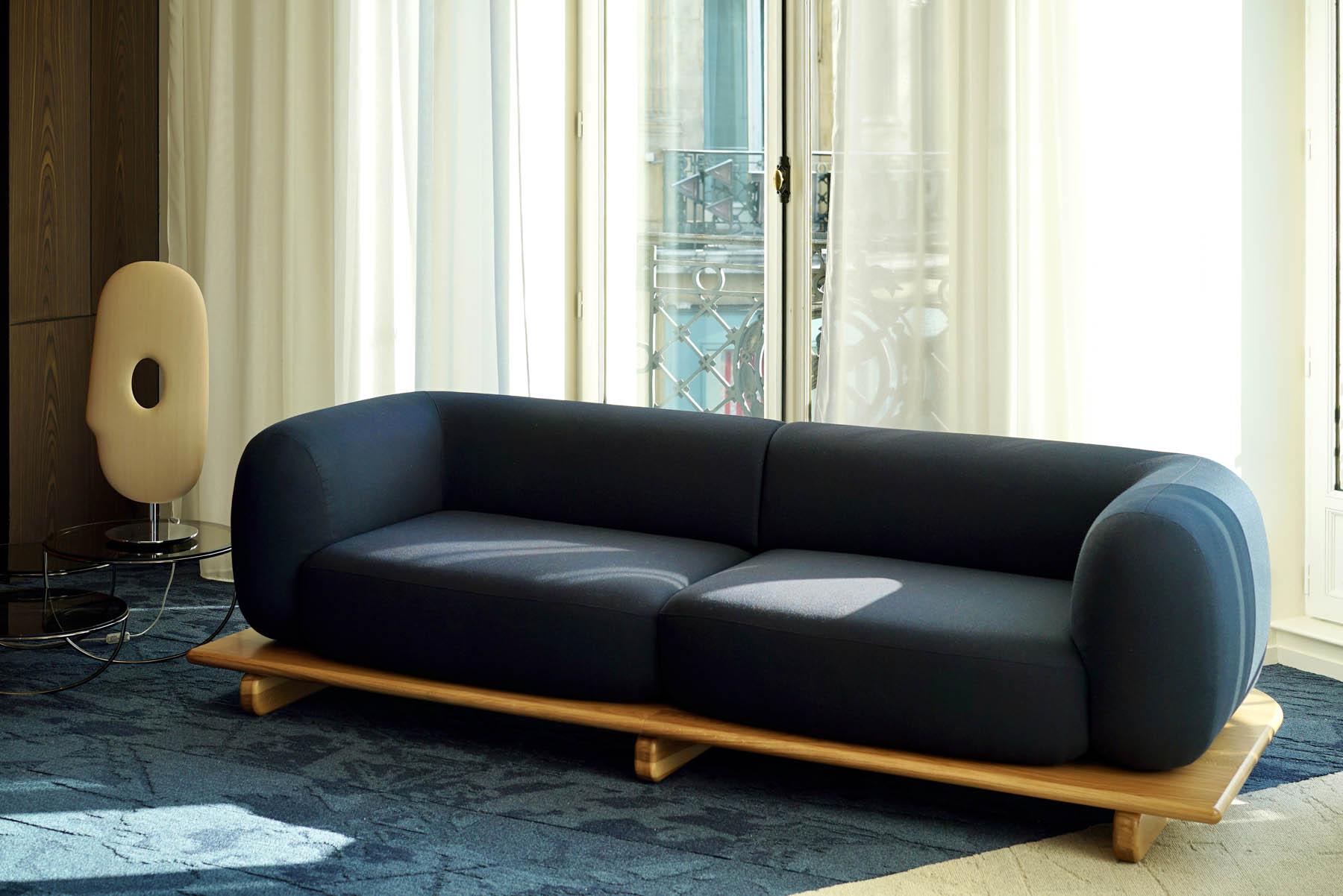 """Canapé / Sofa """"Onigiri"""" en laine posé sur plateau en bois par Louis Denavaut (Cider). Fauteuil """"Calice"""" par Patrick Norguet (La Manufacture)"""