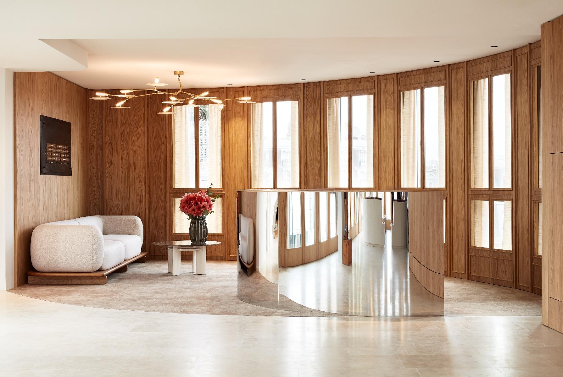 Banque accueil bureaux, lustre laiton et porcelaine par Lindsey Adelman, table basse par socialite family, sol pierre de tala, moquette par Galerie B