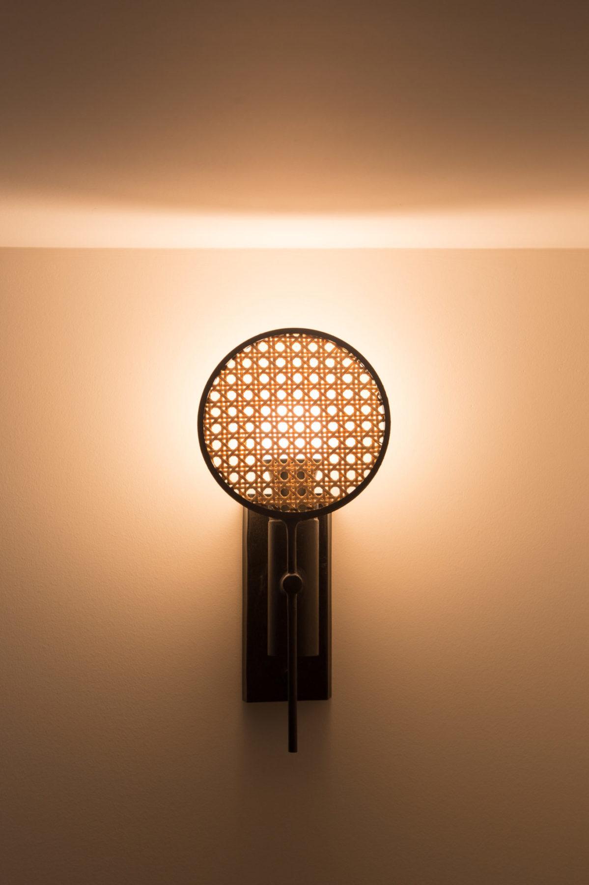 Lampe, applique murale cannage traditionnel en rotin. Vue rapprochée allumée