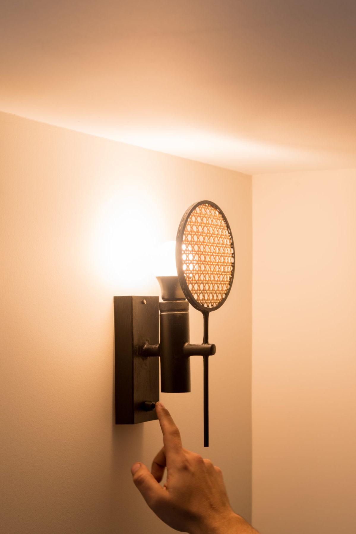 Lampe, applique murale cannage traditionnel en rotin. Vue rapprochée interrupteur
