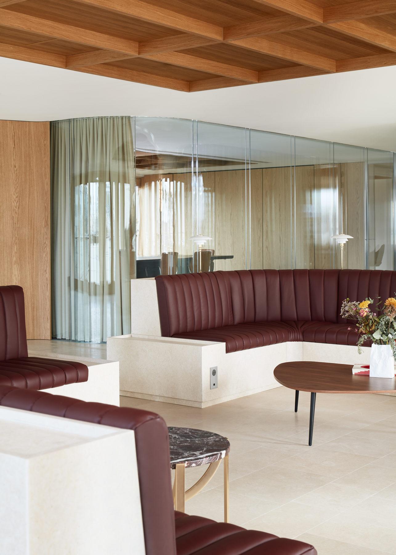 """Lounge bureaux - Banquette en pierre de Tala avec assises en cuir bordeaux, table basse """"Astra"""" en marbre par la Manufacture Patrick Norguet, cloison en verre bombé"""