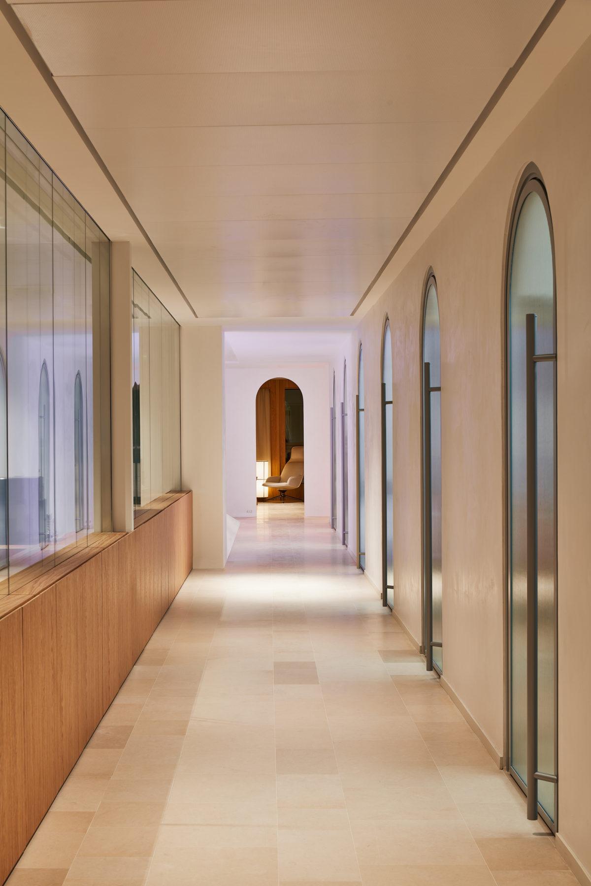 """Couloir avec portes d'arches en verre rainuré acoustique, bâton maréchal, fauteuil """"Assemblage"""" par La Manufacture et design pat Todd Bracher"""