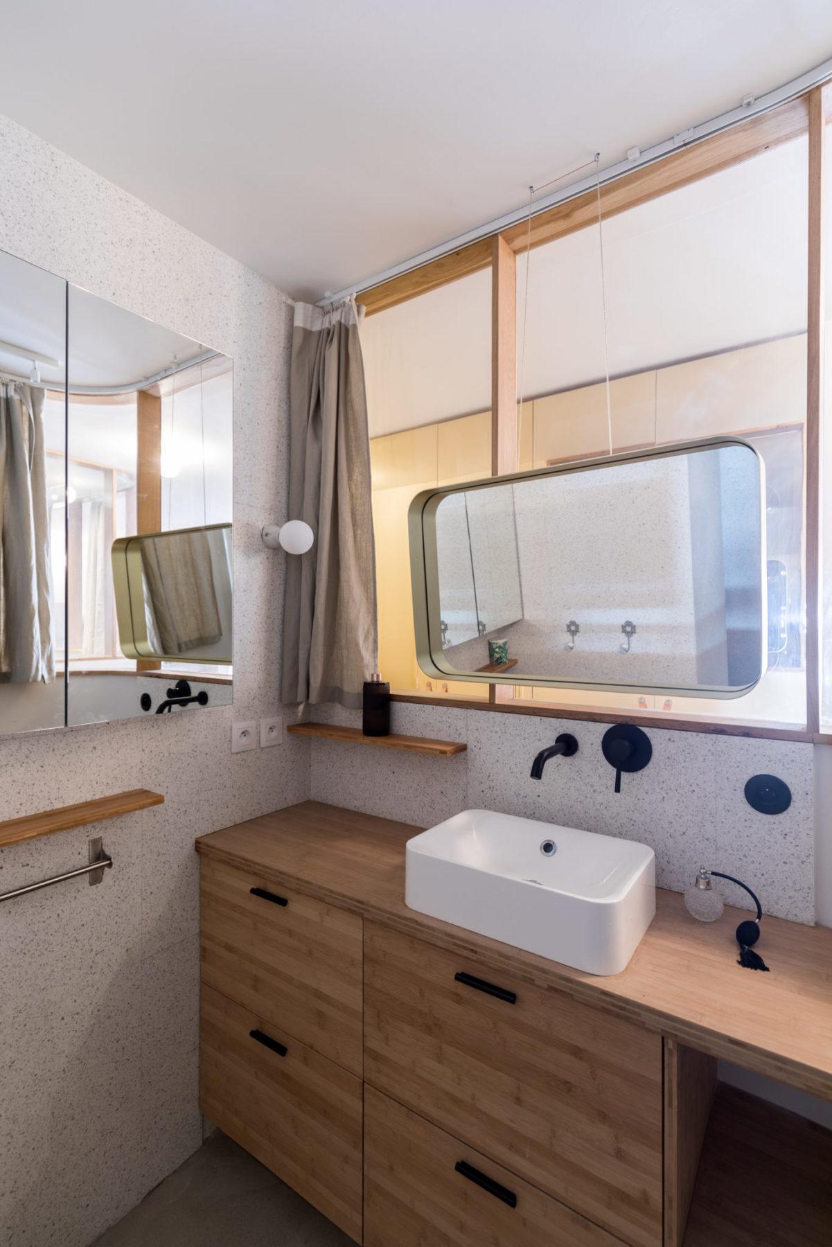 Salle de bains - Miroir suspendu, mur en terrazzo blanc. Meuble /commode en bambou avec vasque
