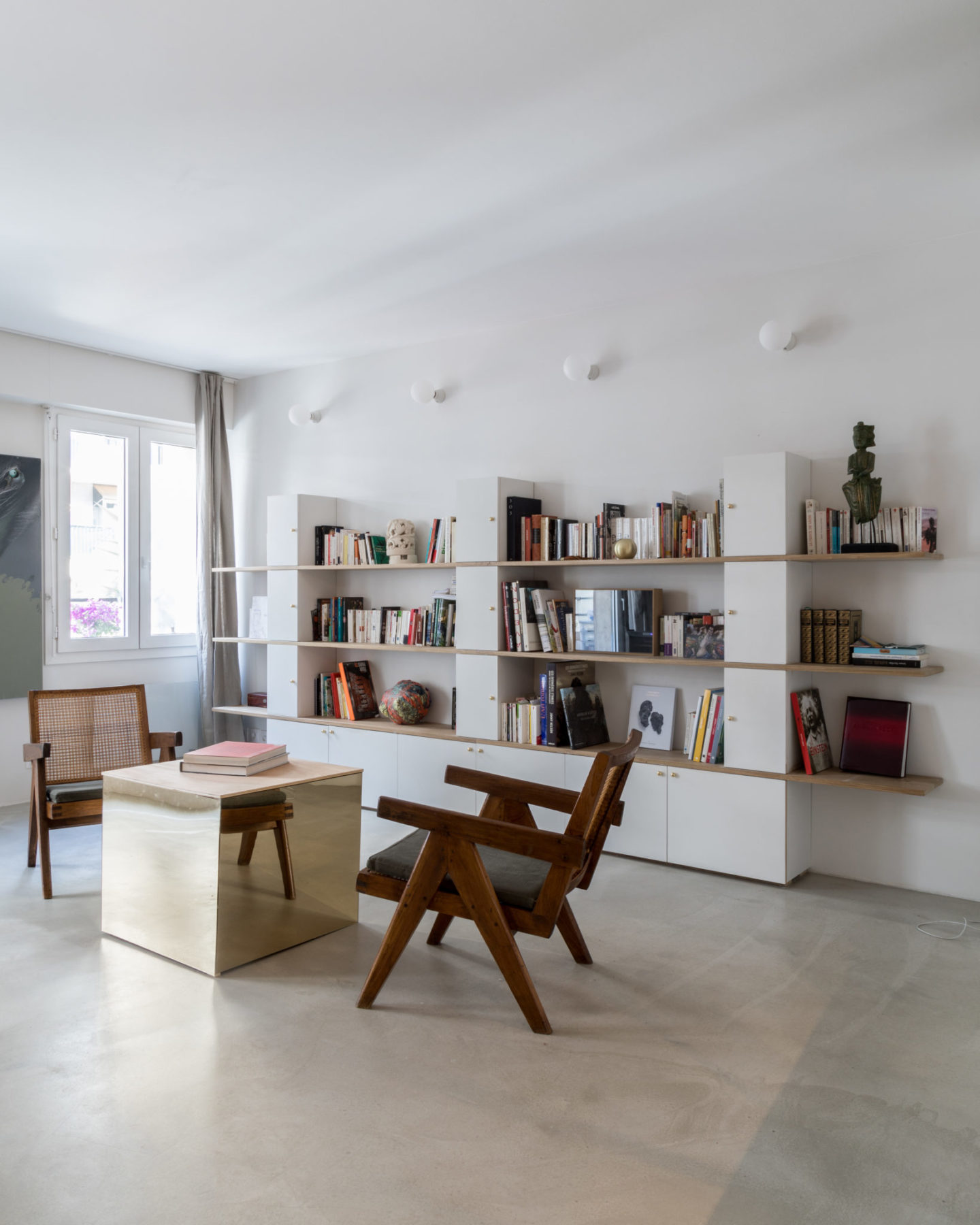 Séjour - Fauteuils Pierre Jeanneret, Le Corbusier. Sol ciment vernis, table cube miroir bronze
