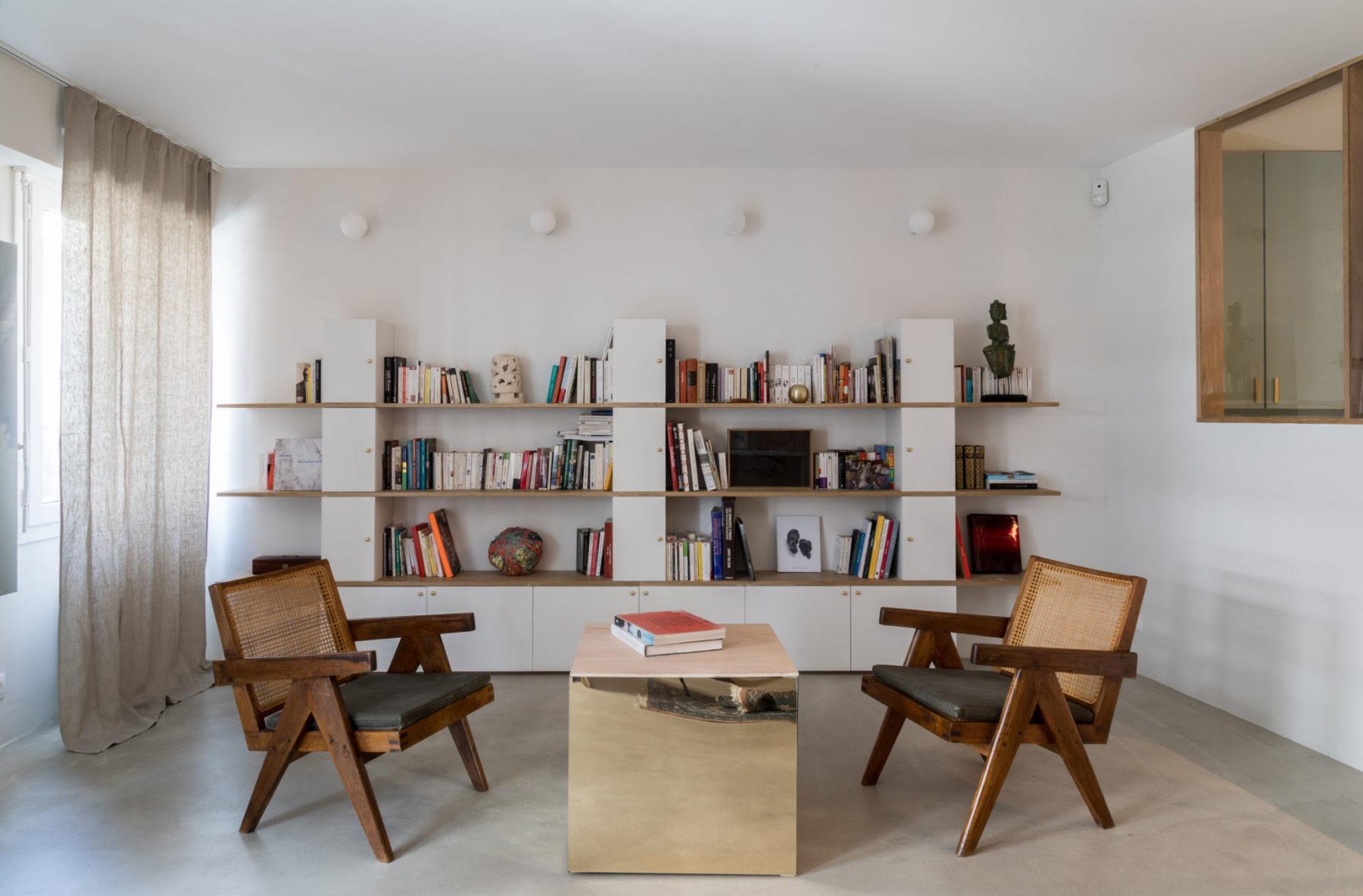 Séjour - Fauteuils Pierre Jeanneret, Le Corbusier. Bibliothèque totem, pelote Sheila hicks, table cube miroir bronze